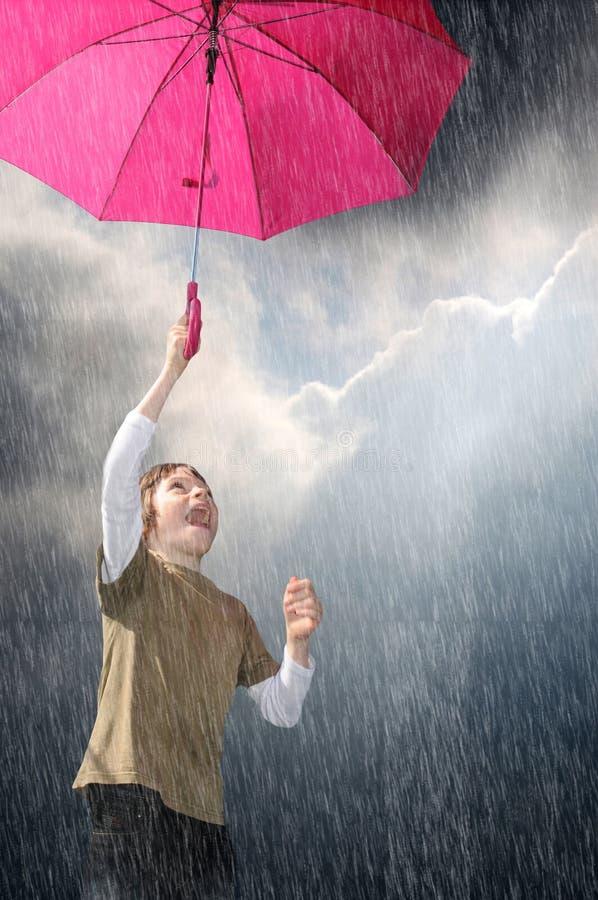 I like the rain, boy with pink umbrella. Boy jumping in the sky with a pink umbrella, he likes playing in the rain
