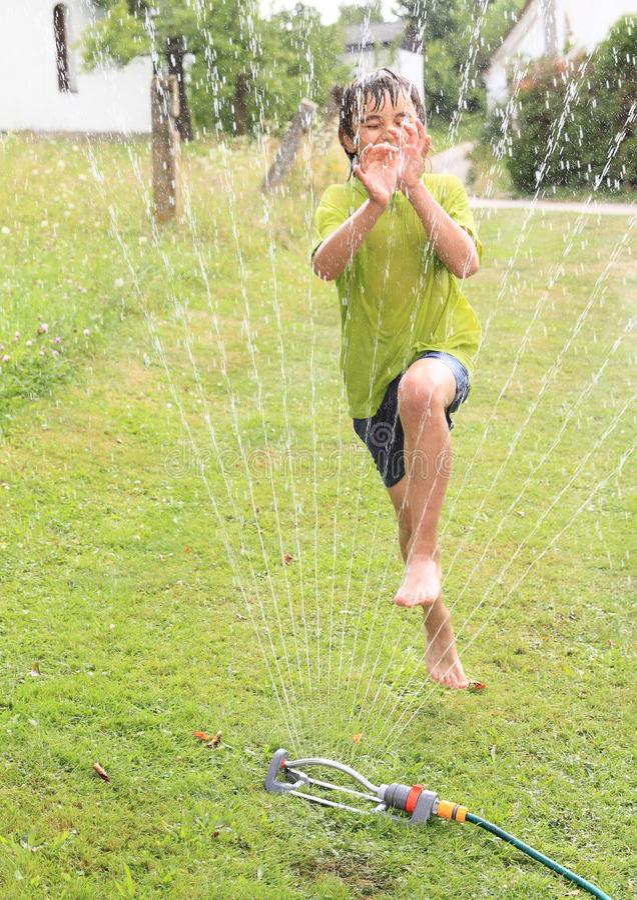 Boy jumping thru sprinkler stock images