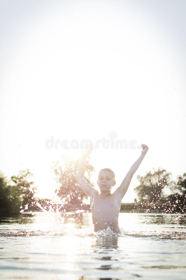 Boy jumping up in lake stock photos