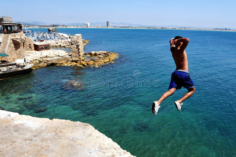 Boy jumps from the ancient walls of Acre royalty free stock images