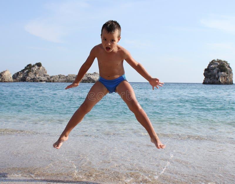 Boy jumps on beach stock photography