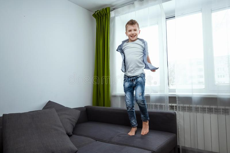 The boy jumps on the couch in the living room, having fun, fooling around, while his parents are not at home. Baby sitting, baby. Alone at home stock photo