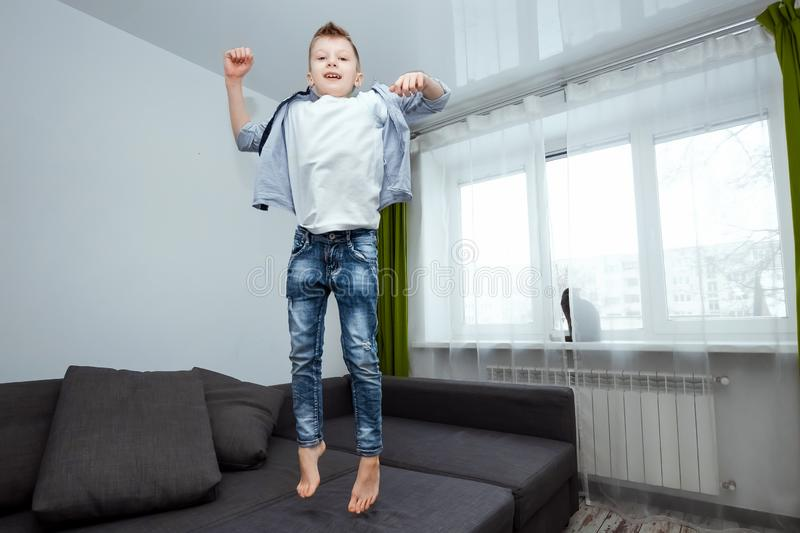 The boy jumps on the couch in the living room, having fun, fooling around, while his parents are not at home. Baby sitting, baby. Alone at home stock image