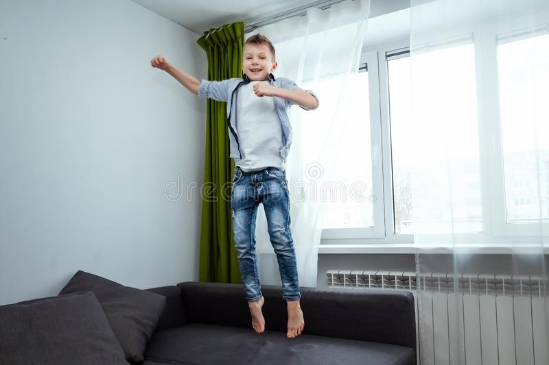 The boy jumps on the couch in the living room, having fun, fooling around, while his parents are not at home. Baby sitting, baby. Alone at home royalty free stock photography