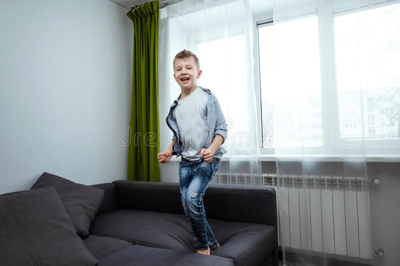 The boy jumps on the couch in the living room, having fun, fooling around, while his parents are not at home. Baby sitting, baby. Alone at home royalty free stock photo