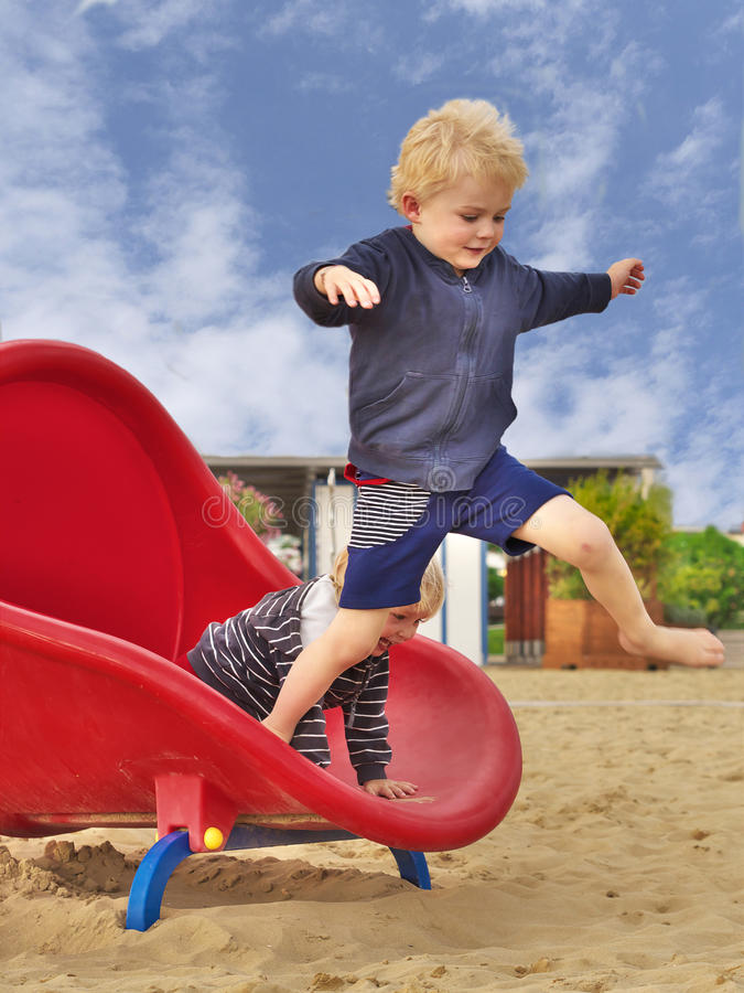 Boy jumps off slide stock photo