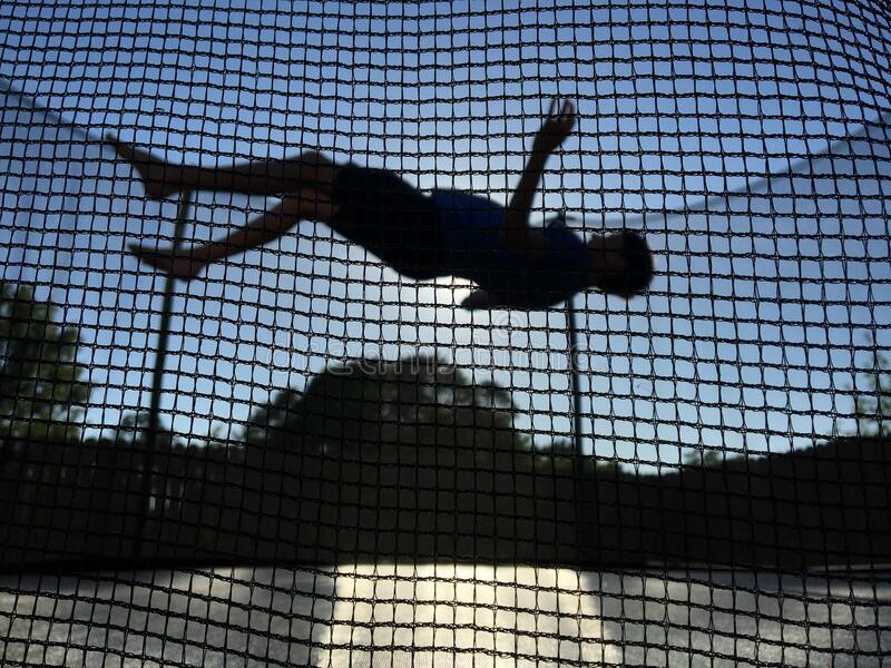 Silhouetted trampoline jumper royalty free stock image