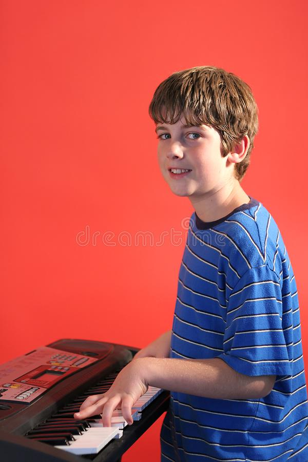 Boy on keyboard right vertical stock image