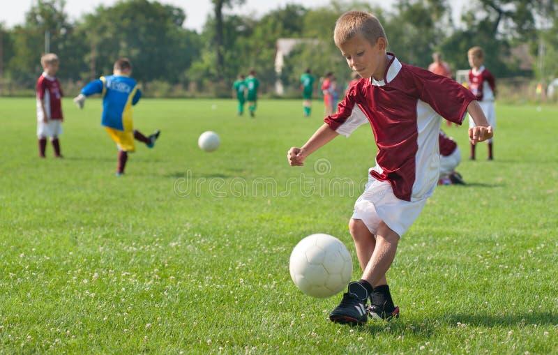 Boy kicking football royalty free stock photography