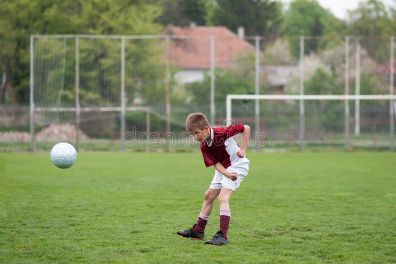 Boy kicking football stock photo