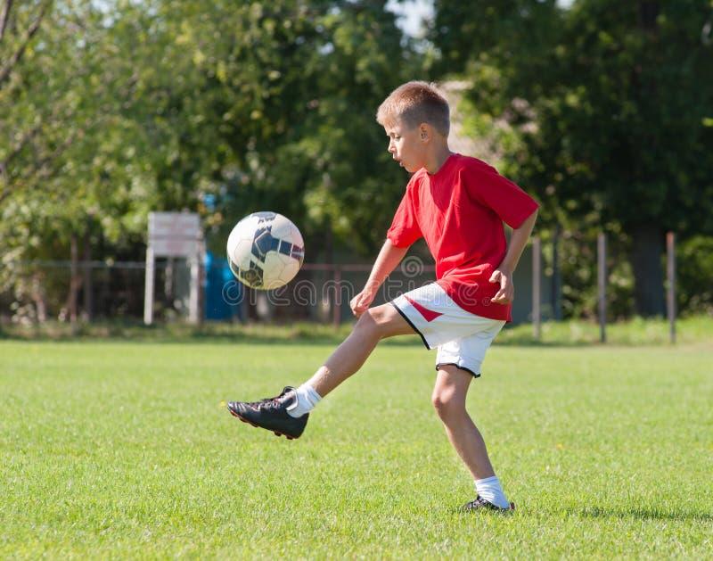 Boy kicking football stock image