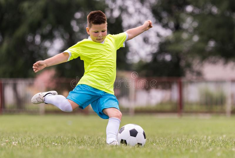 Boy kicking football on the sports field stock image