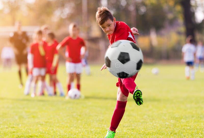 Boy kicking football on the sports field royalty free stock photos
