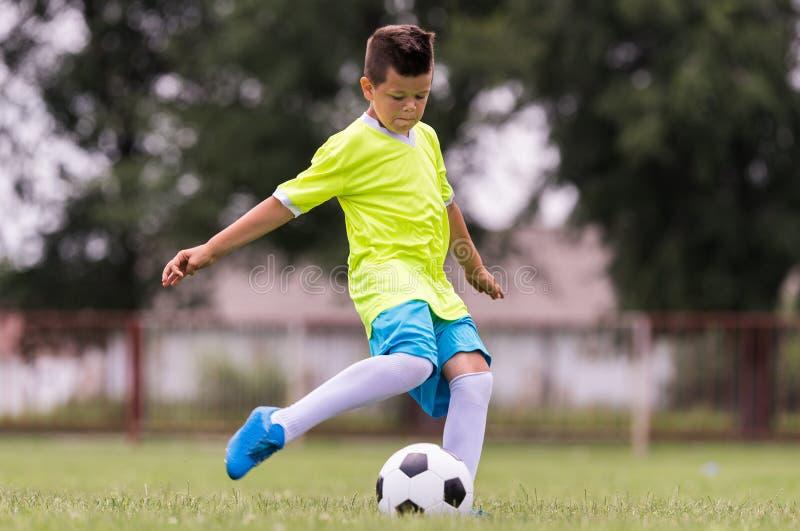 Boy kicking football on the sports field royalty free stock photography