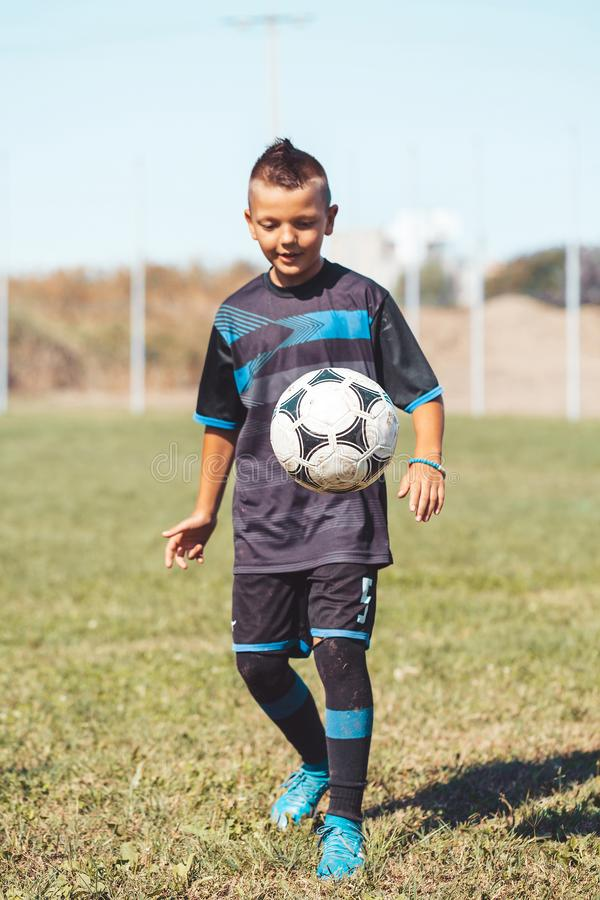 Boy kicking football on the sports field during soccer training. Focus on the ball stock photos