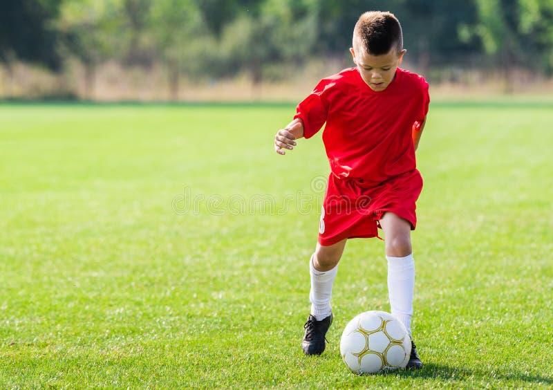 Boy kicking soccer ball. On sports field stock photos