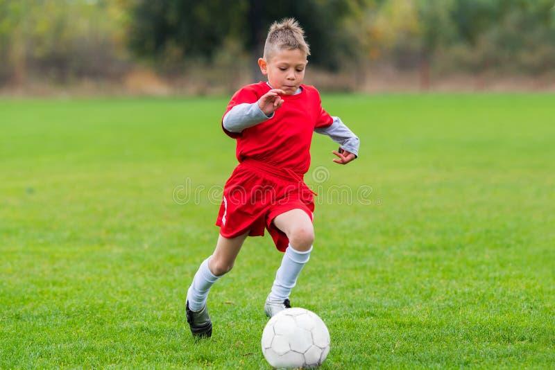 Boy kicking soccer ball royalty free stock image
