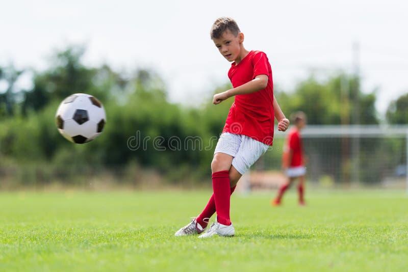 Boy kicking soccer ball stock photography