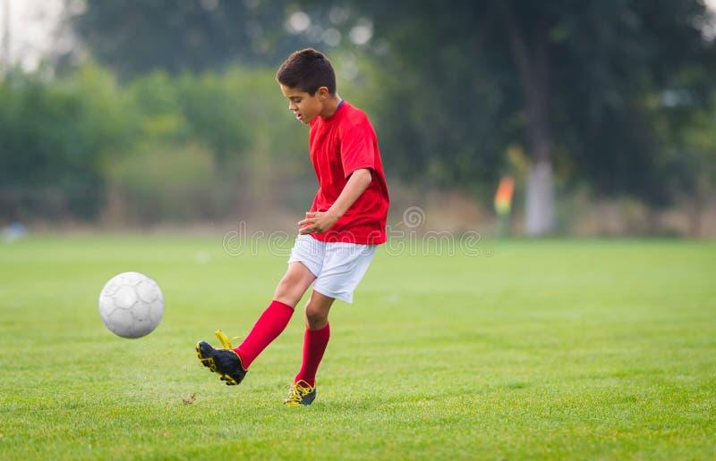 Boy kicking soccer ball stock image