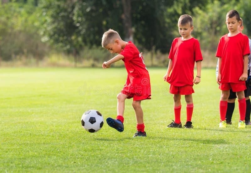 Boy kicking soccer ball at training stock image