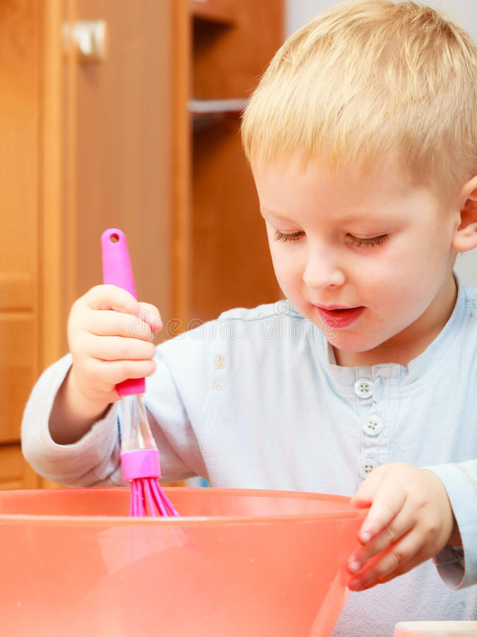 Boy kid baking cake. Child beating dough with wire whisk. Kitchen. stock photo