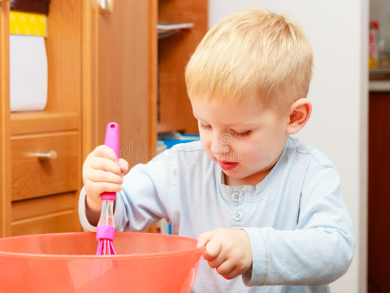 Boy kid baking cake. Child beating dough with wire whisk. Kitchen. royalty free stock photos