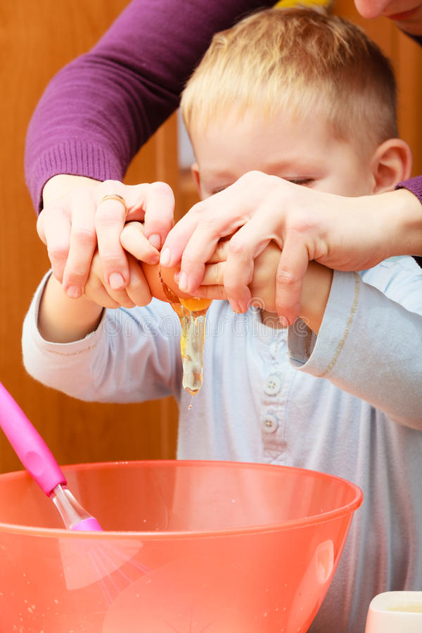 Boy kid baking cake. Child breaking egg into a bowl. Kitchen. royalty free stock photos