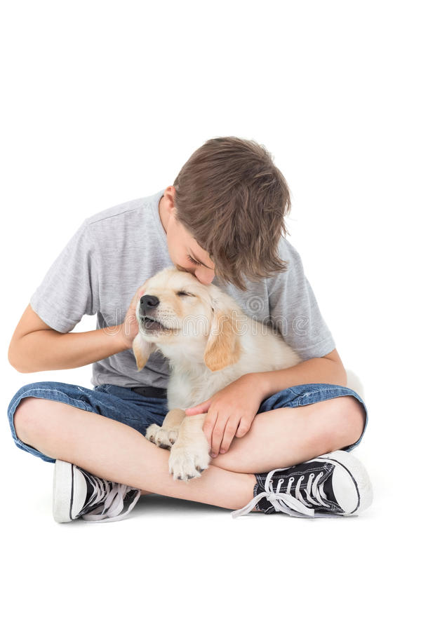 Boy kissing puppy over white background stock photos