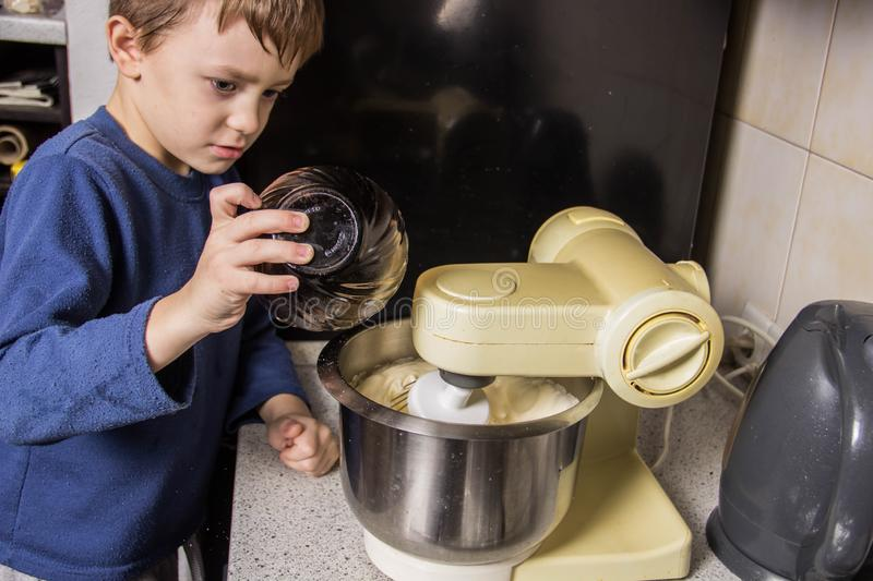 The boy in the kitchen kneads the dough for cupcakes in the mixer, adding ingredients stock photos