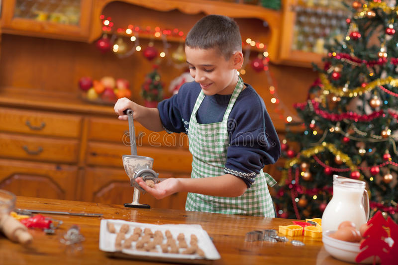 Boy in the kitchen preparing Christmas cookies. Boy with machine mold macking cookies in Xmas stock photography