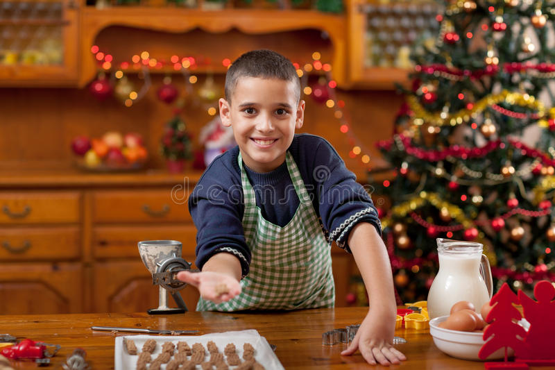 Boy in the kitchen preparing Christmas cookies. Boy with machine mold macking cookies in Xmas royalty free stock photos