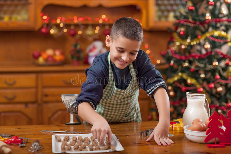 Boy in the kitchen preparing Christmas cookies. Boy with machine mold macking cookies in Xmas royalty free stock photography