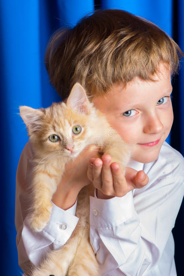 The boy with the kitten. A boy with ginger kitten on hand pressed against the cheek stock image