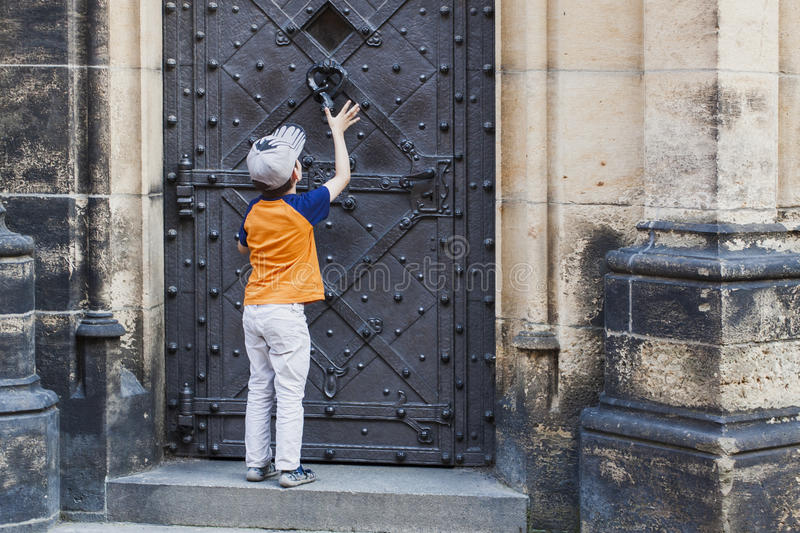 Boy knocking in door knocker on old medieval castle. Textured stone walls. kid begging for entrance to the house royalty free stock image