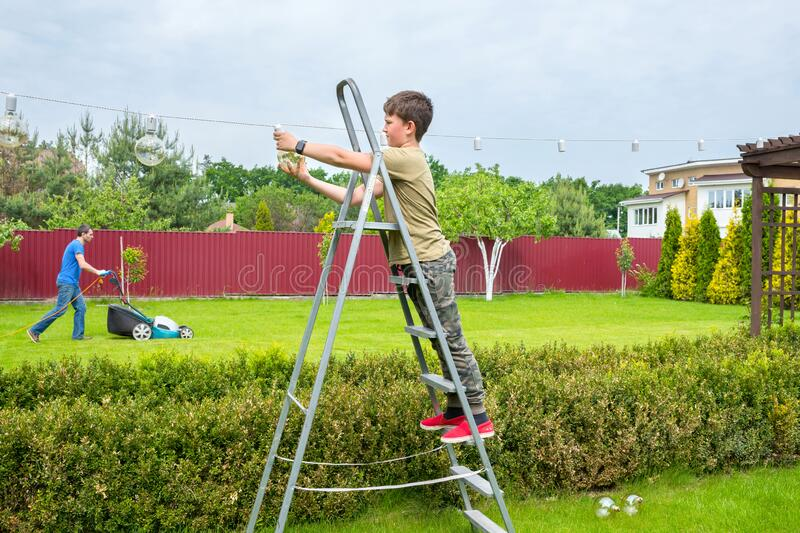 A boy on the ladder is plugging in incandescent lamps in the backyard. Holiday preparation. A family is cleaning the garden.  royalty free stock photo