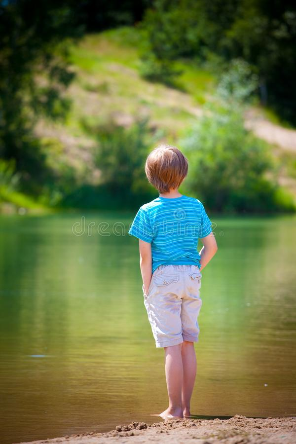 Boy on lakeside royalty free stock photography