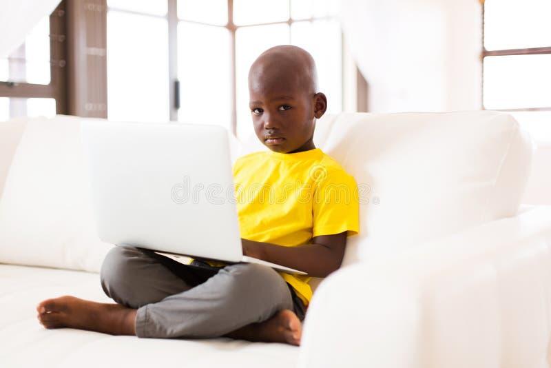 Boy laptop computer. Adorable little african american boy using laptop computer at home stock images