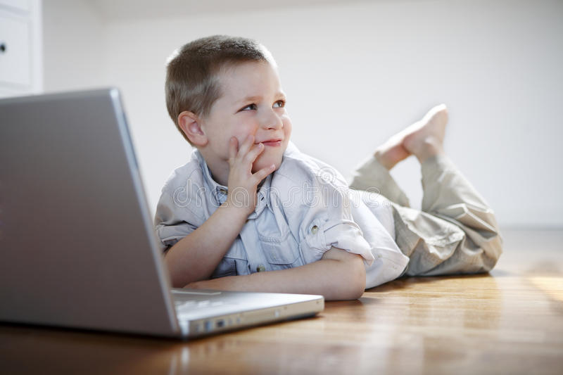 Boy with laptop computer laying down on the floor royalty free stock image