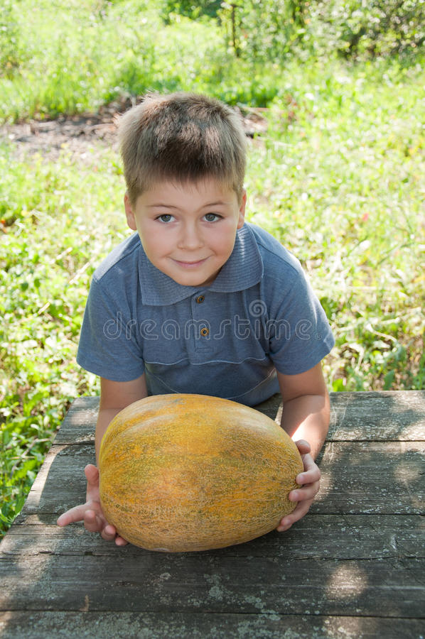 A Boy With A Large Melon Royalty Free Stock Photos