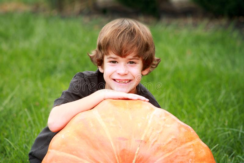 Boy and Large Pumpkin royalty free stock images