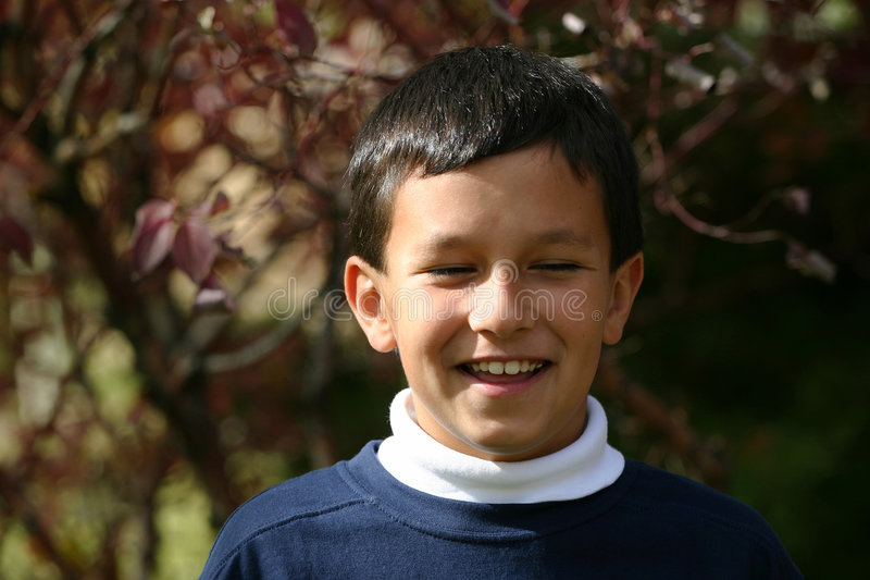 Boy Laughing. A young 9 year old Hispanic American boy laughing. Taken outside during the Fall season, red leaves behind, he wears a white turtleneck shirt and royalty free stock photo
