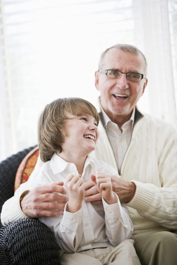 Boy laughing with grandfather. Portrait of 9 year old boy laughing with grandfather royalty free stock photography