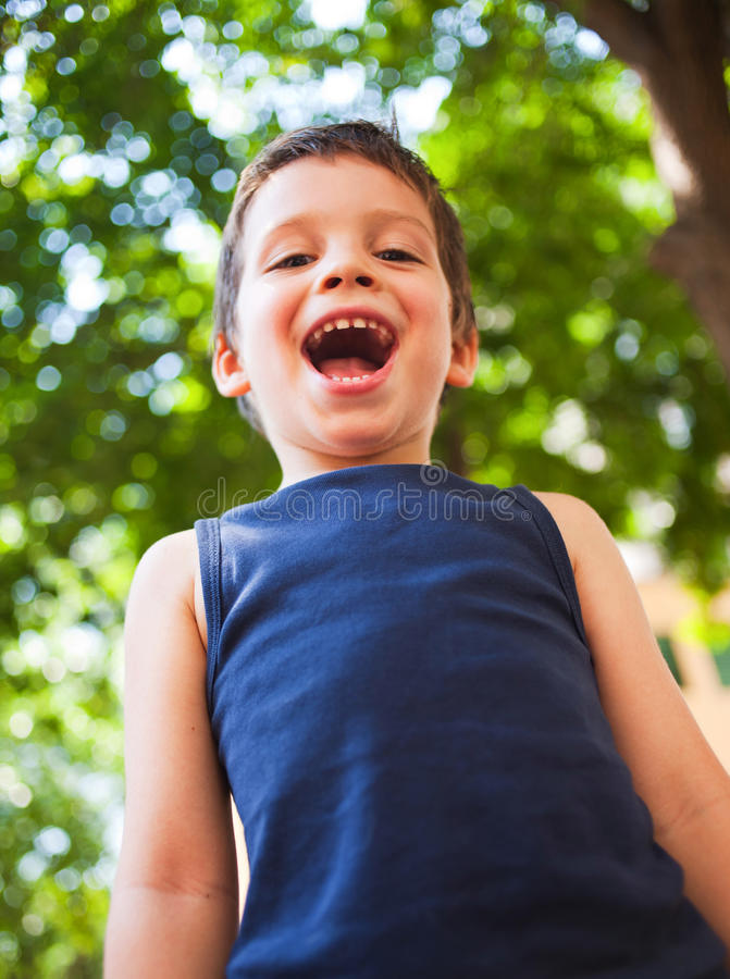 Boy laughing in park stock photography