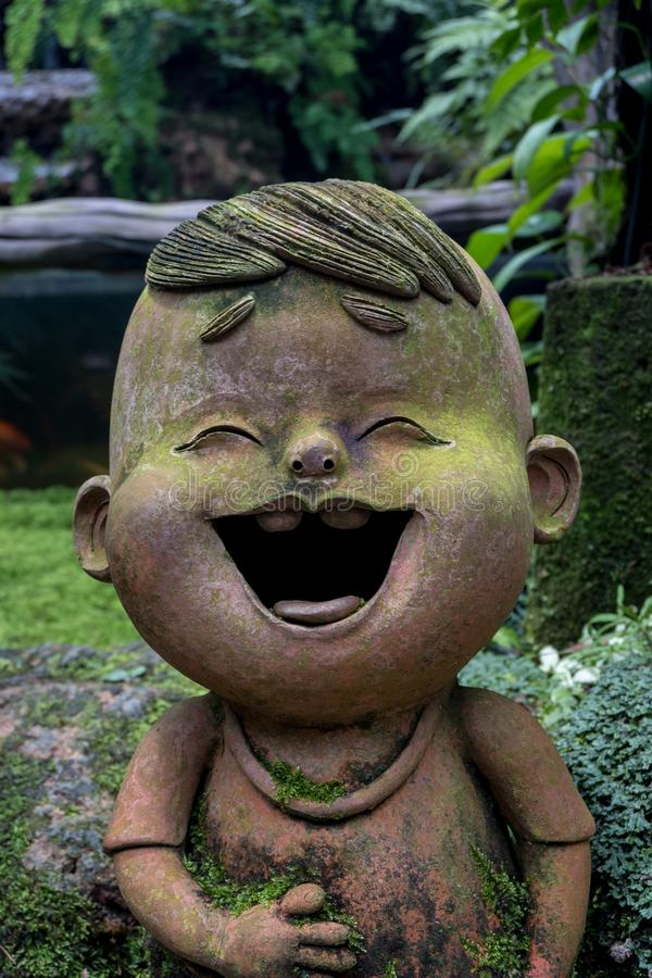 Boy is laughing statue in flower garden. Close up of boy is laughing statue in flower garden stock photos