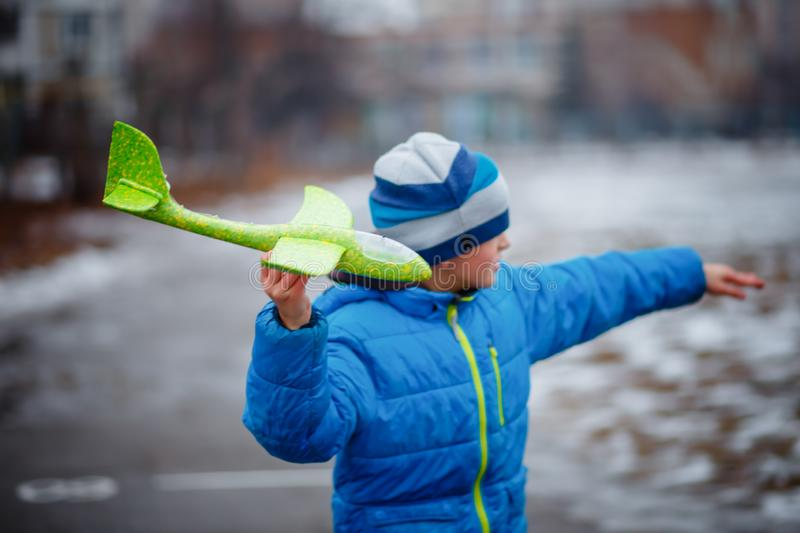 The boy launches a glider plane green in winter. Active games on the air. Airplane flights. Traveling in the winter royalty free stock photos