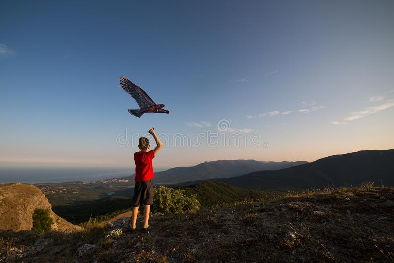 The boy launches a kite. Beautiful sunset. Mountains, sea, landscape. The boy in the red t-shirt and shorts. Summer day stock photo