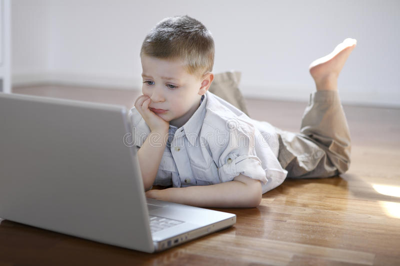 Boy laying down on the floor with laptop computer royalty free stock photo