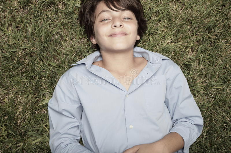 Boy laying on grass stock images