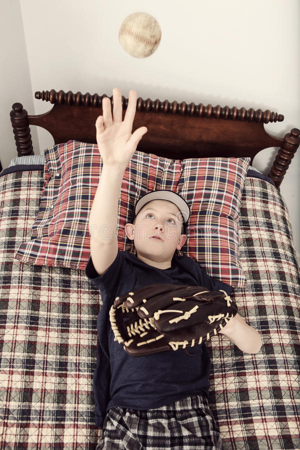 Boy laying on his bed waiting for baseball season royalty free stock photography