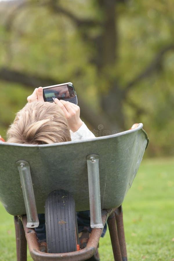 Boy Laying Wheelbarrow Using Mobile Phone stock photos